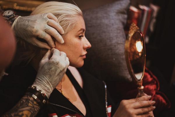 A cantora Christina Aguilera sem maquiagem colocando um piercing (Foto: Twitter)