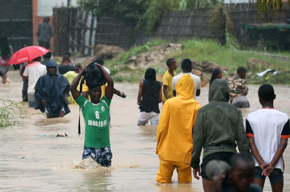 Moradores de Pemba, em Moçambique, atravessam uma via inundada nesta segunda (29), após a passagem do ciclone Kenneth. — Foto: Mike Hutchings/Reuters