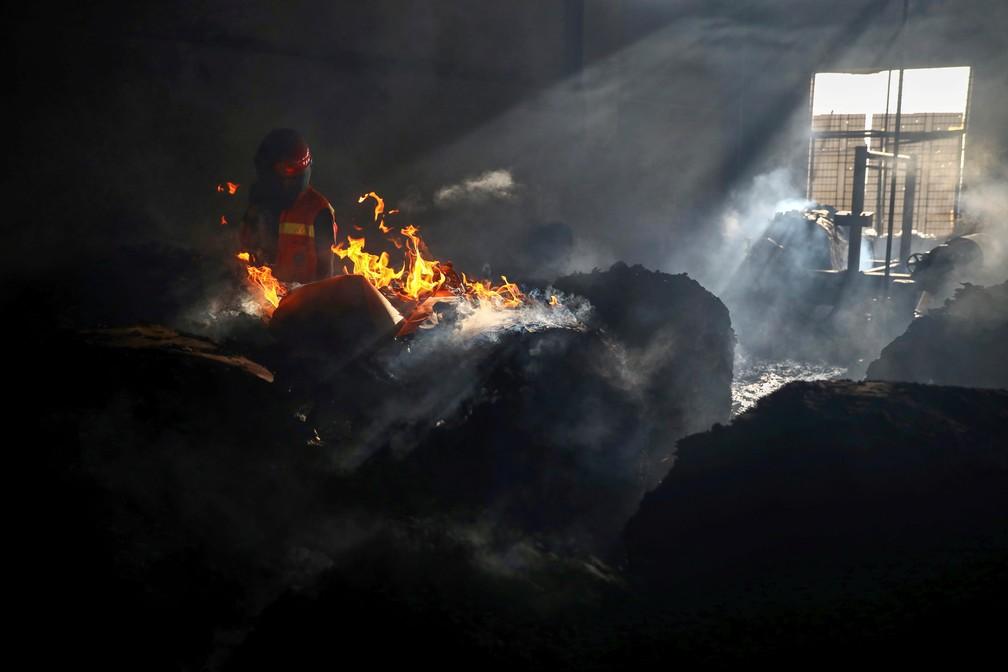Bombeiro tenta extinguir incêndio dentro do prédio de fábrica em Rupganj, nos arredores de Daca, capital de Bangladesh, em 9 de julho de 2021 — Foto: Mohammad Ponir Hossain/Reuters