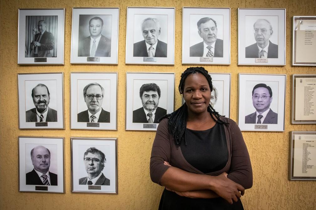 A professora Adriana Alves, diante de retratos dos diretores do Instituto de Geociências da USP — Foto: Fábio Tito/G1