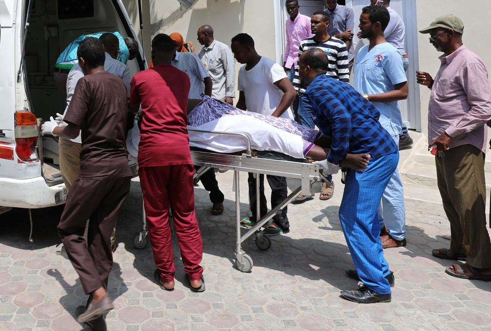Paramédicos transportam homem ferido em ataque nesta sexta-feira (9) perto de hotel em Mogadiscio  — Foto: Feisal Omar/Reuters