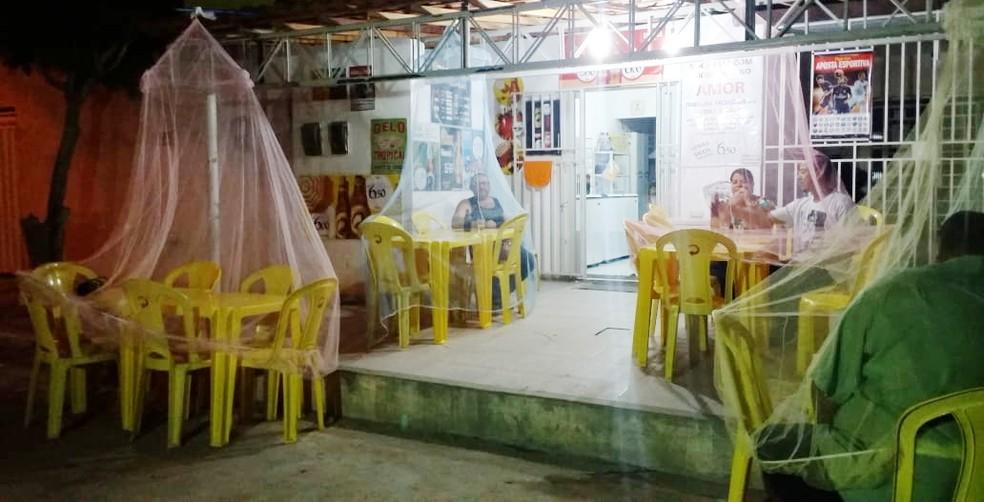 Proprietária de bar em Petrolina usa mosquiteiros nas mesas para proteger clientes das muriçocas. (Foto: Clédiston Ancelmo/TV Grande Rio)