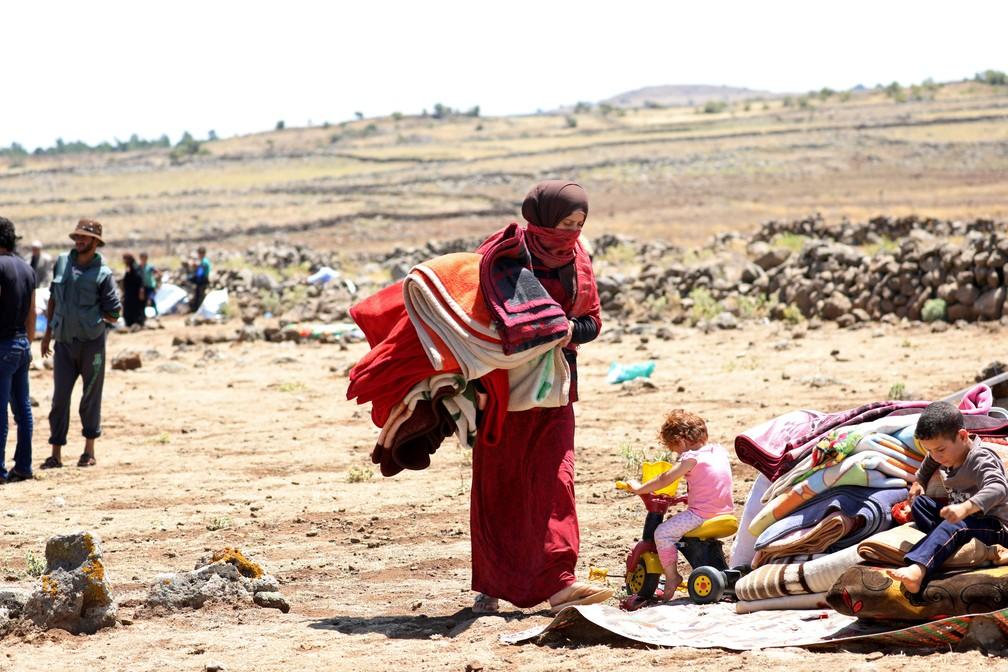 Deslocados internos da província de Deraa carrega cobertores em Quneitra, perto do território das colinas de Golã (Foto: Alaa al-Faqir/Reuters)