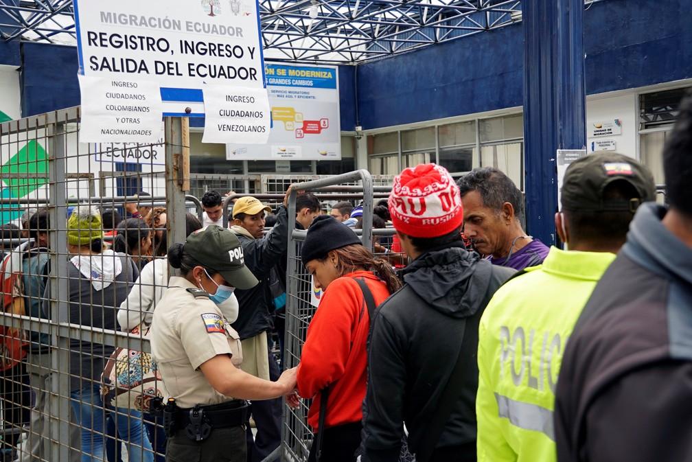 Agentes de fronteira do Equador verificam documentos de migrantes venezuelanos na fronteira com a Colômbia — Foto: Daniel Tapia/Reuters