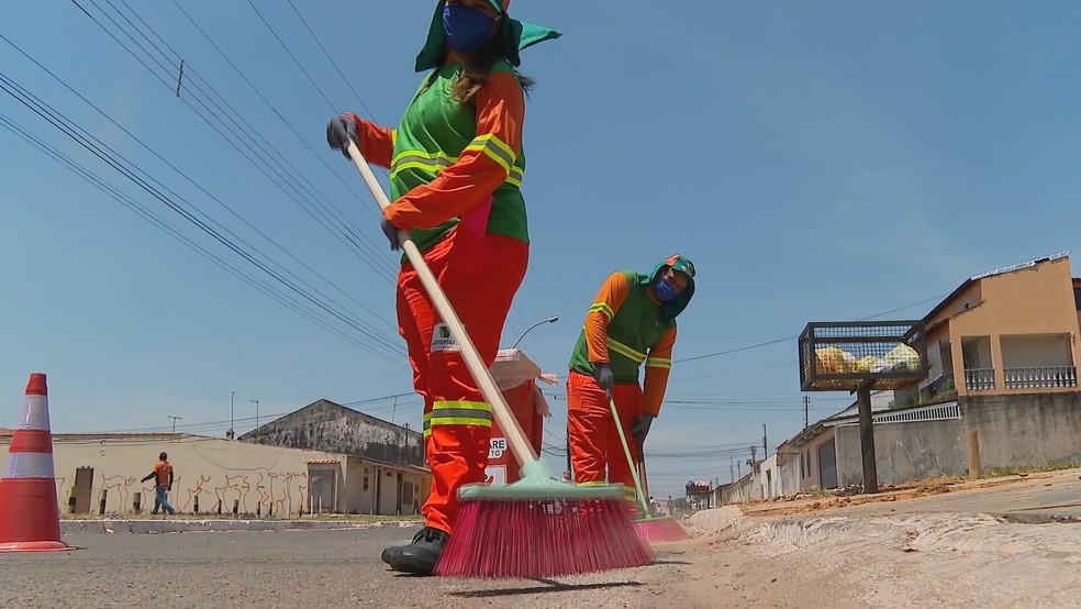 Funcionários do SLU trabalham em rua do DF — Foto: TV Globo