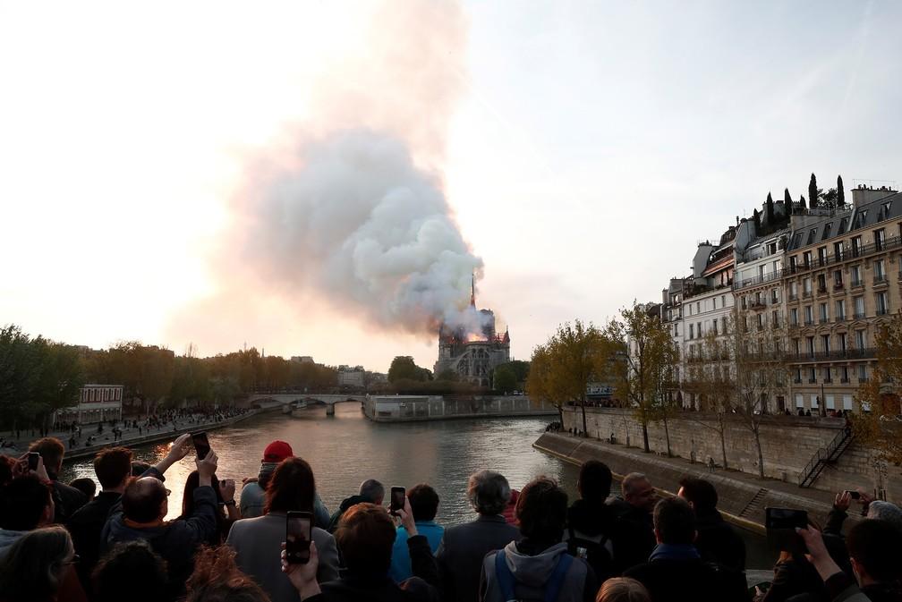 Pessoas observam de longe o incêndio na Catedral de Notre-Dame, em Paris — Foto: Benoit Tessier/Reuters