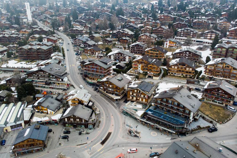 VERBIER (Suíça) - Carros de patrulha da polícia suíça são vistos em uma rua vazia da estação de esqui durante o surto de doença por coronavírus em Verbier nesta terça-feira (24)  — Foto:   Laurent Darbellay/Keystone via AP