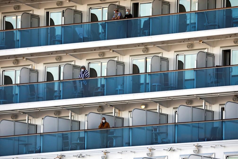Passageiros de navio em quarentena atracado em Yokohama, no Japão, permanecem nas varandas das cabines nesta terça-feira (19) — Foto: Athit Perawongmetha/Reuters