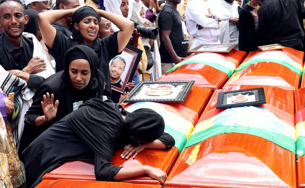 Mulheres choram ao lado de caixão durante funeral simbólico das vítimas do desastre com avião da Ethiopian Airlines, na Igreja Ortodoxa da Santíssima Trindade, em Addis Abeba, na Etiópia, neste domingo (17)  — Foto: Tiksa Negeri/ Reuters