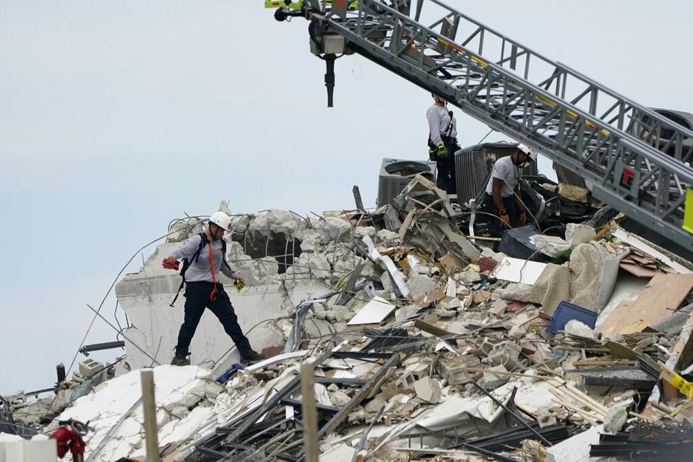 Socorristas vasculham escombros de prédio que caiu em Surfside, na região de Miami, nesta quinta-feira (24) — Foto: Lynne Sladky/AP Photo