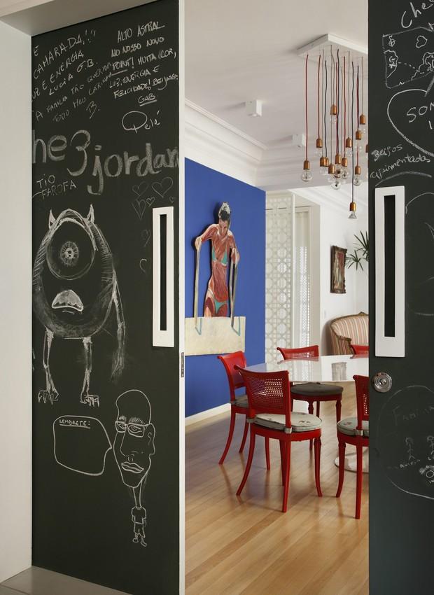 A porta de correr, entre a cozinha e a sala de jantar, foi pintada com tinta preta fosca. Por isso, pode receber desenhos e recados feitos com giz. Projeto do arquiteto Felipe Rio Branco (Foto: Denilson Machado/MCA Estúdio)