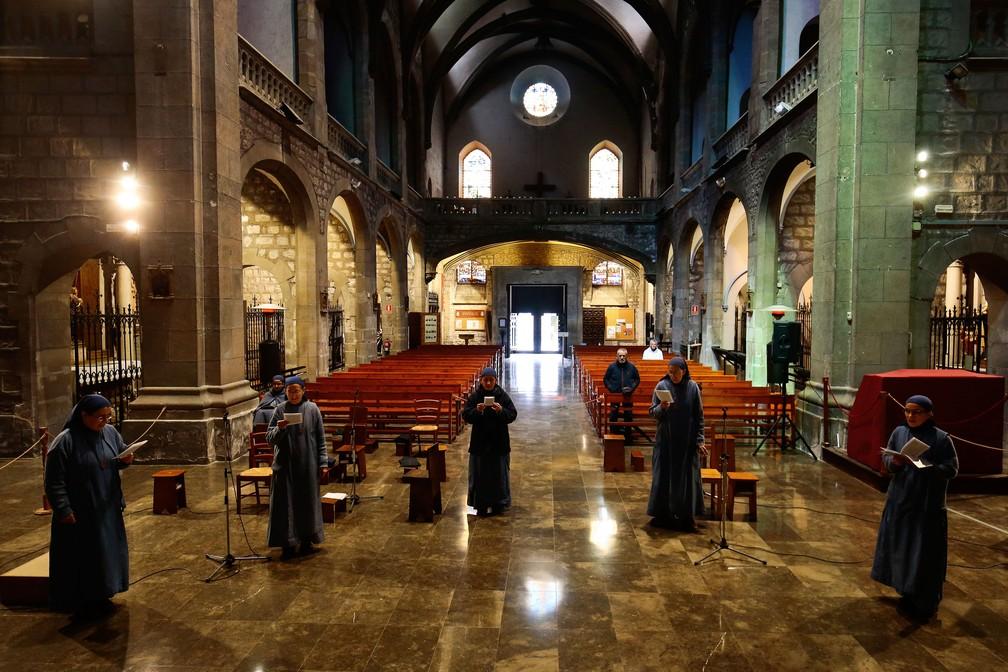 Freiras cantam em uma igreja quase vazia em Barcelona, na Espanha, no domingo (29)  — Foto: Pau Barrena / AFP
