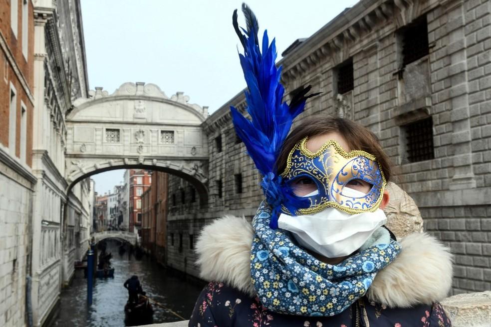 Em Veneza, turista usa uma máscara de carnaval e uma de proteção contra o coronavírus; o evento foi cancelado no país — Foto: Andrea Pattaro / AFP