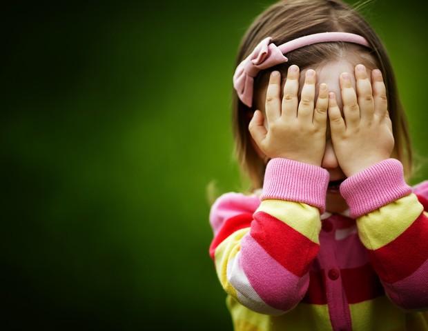 Criança escondendo o rosto com as mãos (Foto: Shutterstock)