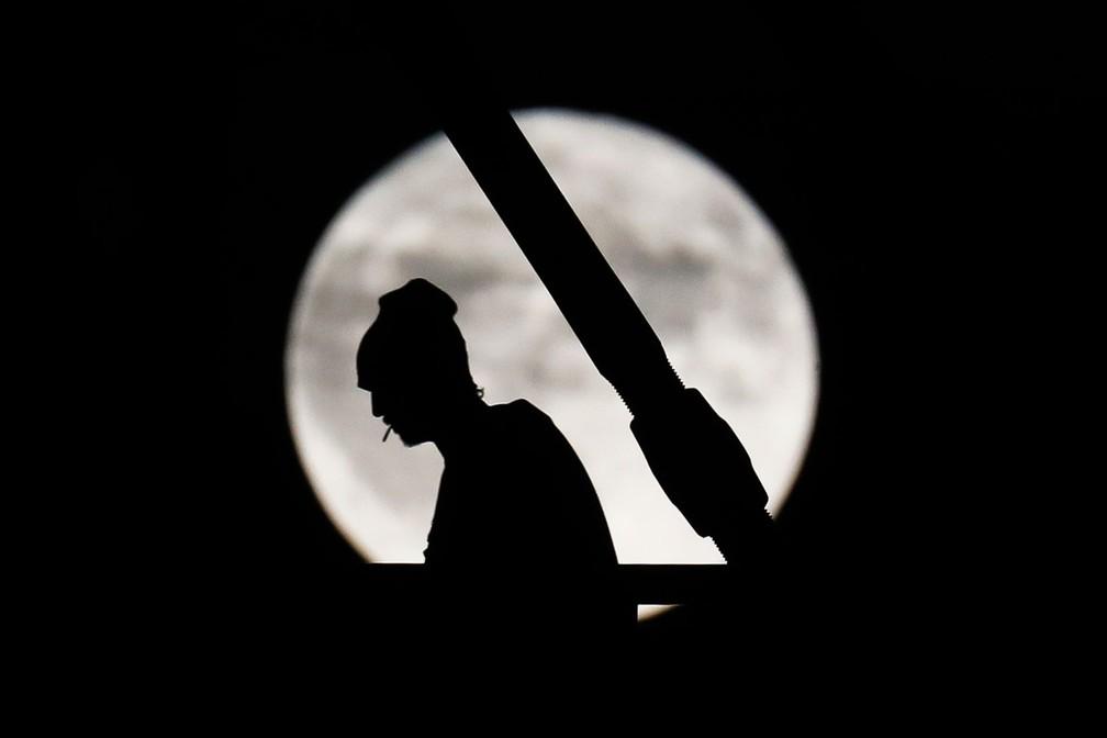 -  Pedrestre caminha em Cincinnati, Ohio, nos EUA, com a lua cheia ao fundo  Foto: John Minchillo/AP
