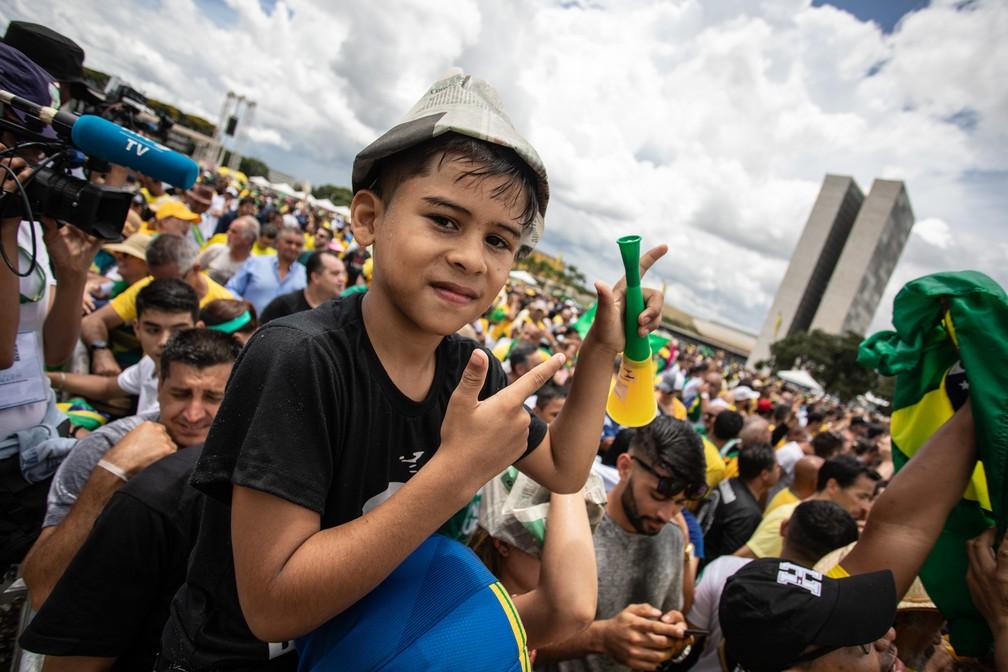 Menino posa para foto fazendo armas com as mãos sobre os ombros de um familiar na Praça dos Três Poderes — Foto: Fábio Tito/G1