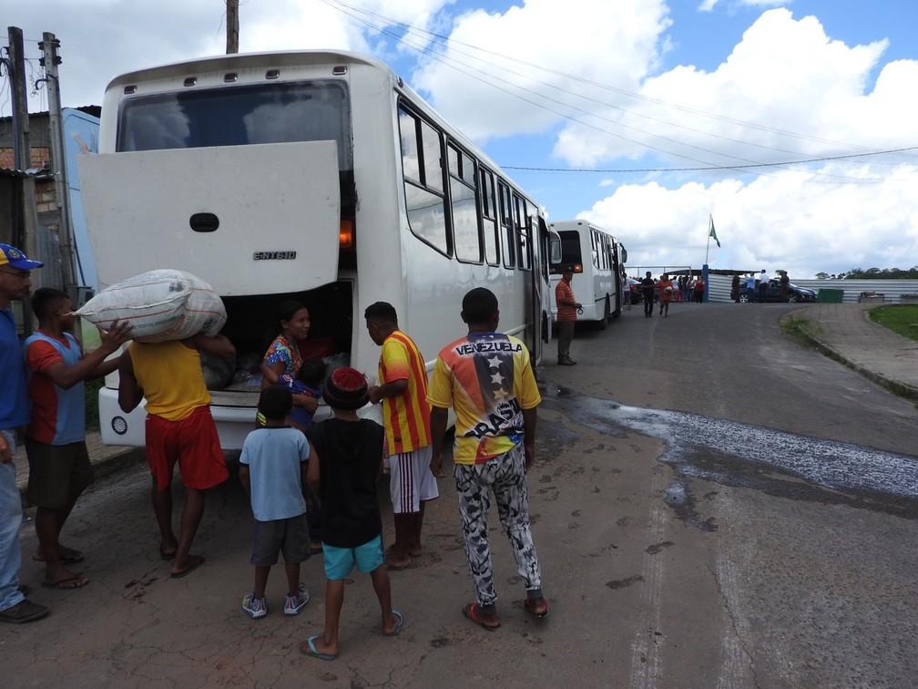 Indígenas Warao colocam os pertences em ônibus do governo venezuelano para irem embora de Pacaraima, em Roraima (Foto: Alan Chaves/G1 RR)