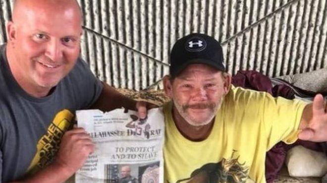 Carlson posa ao lado de Phil, após sua entrevista de emprego, segurando uma reportagem local sobre a história (Foto: Tallahasse Police Department/Facebook via BBC News Brasil)
