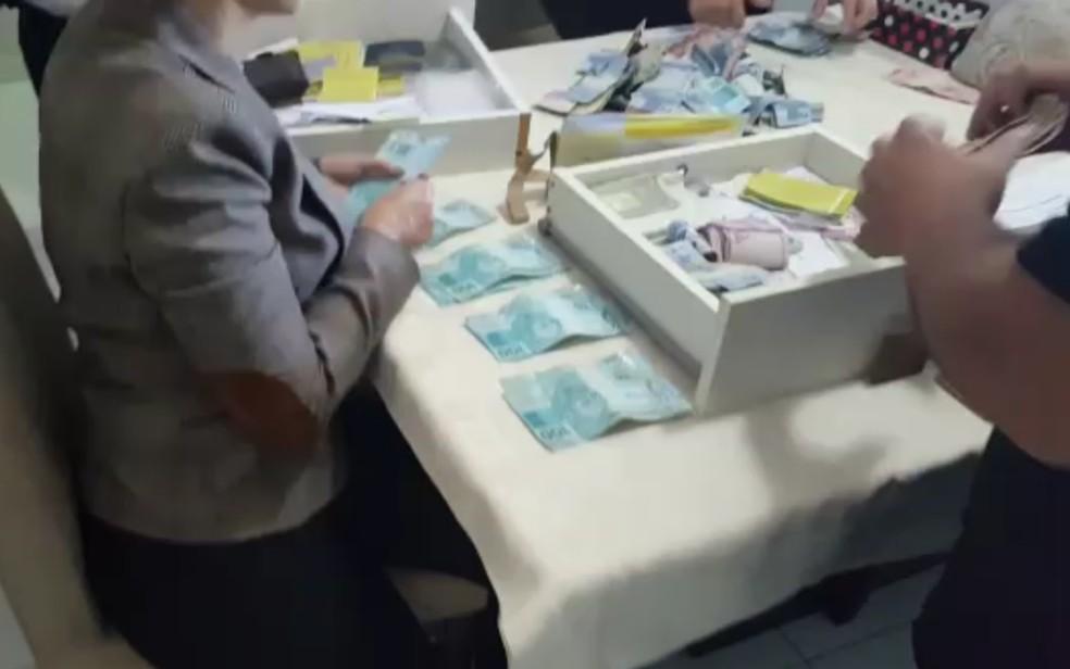 Dinheiro apreendido com fundo falso de guarda-roupa do monsenhor preso em operação contra desvios na Igreja Católica, em Goiás (Foto: TV Anhanguera/Reprodução)