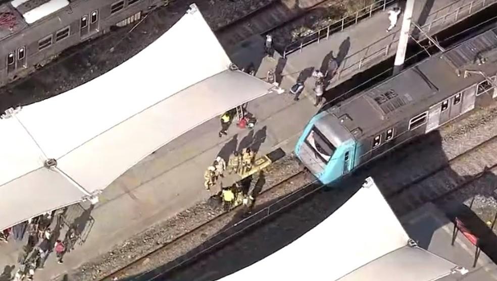 Vítima é socorrida pelos bombeiros na linha do trem na estação do Maracanã — Foto: Reprodução