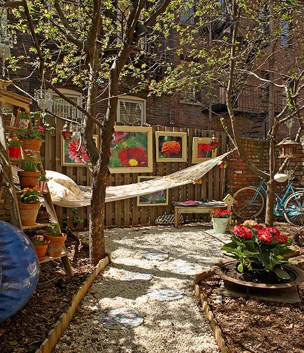 O duplex da designer de interiores Barbara Saulzman tem até jardim. Aqui, o caminho de pedriscos leva à rede com almofadas. Presos à cerca de madeira estão quadros feitos com molduras antigas e fotografias de flores (Foto: Victor Fernandes Ohlif/Casa e Jardim)