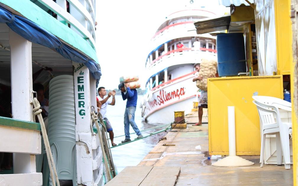 Carregadores de mercadorias se equilibram em rampas de madeira sobre o Rio Negro para entregar produtos em barcos atracados  (Foto: Leandro Tapajós/G1 AM)