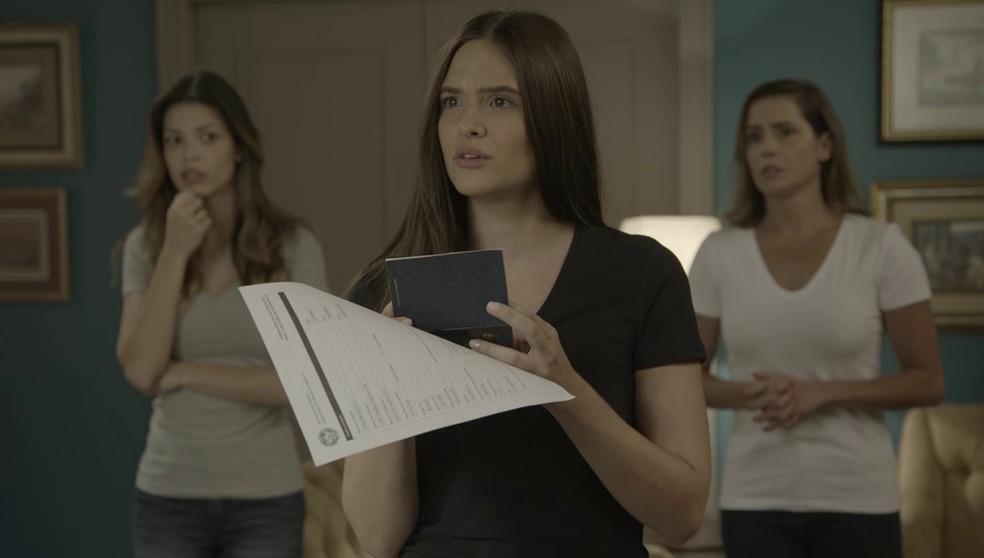 Luna (Juliana Paiva) recebe seu novo passaporte em 'Salve-se Quem Puder' — Foto: Globo