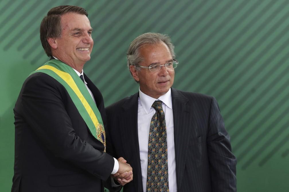 O presidente da República, Jair Bolsonaro, cumprimenta o ministro da Economia, Paulo Guedes, durante a cerimônia de posse ministerial, no Palácio do Planalto, em Brasília — Foto: Eraldo Peres/AP