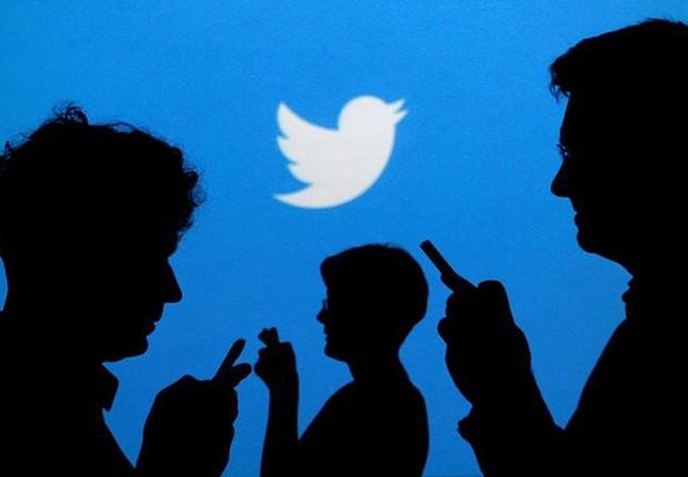 Pessoas usam celulares diante de logo do Twitter  (Foto: Kacper Pempel/Reuters)