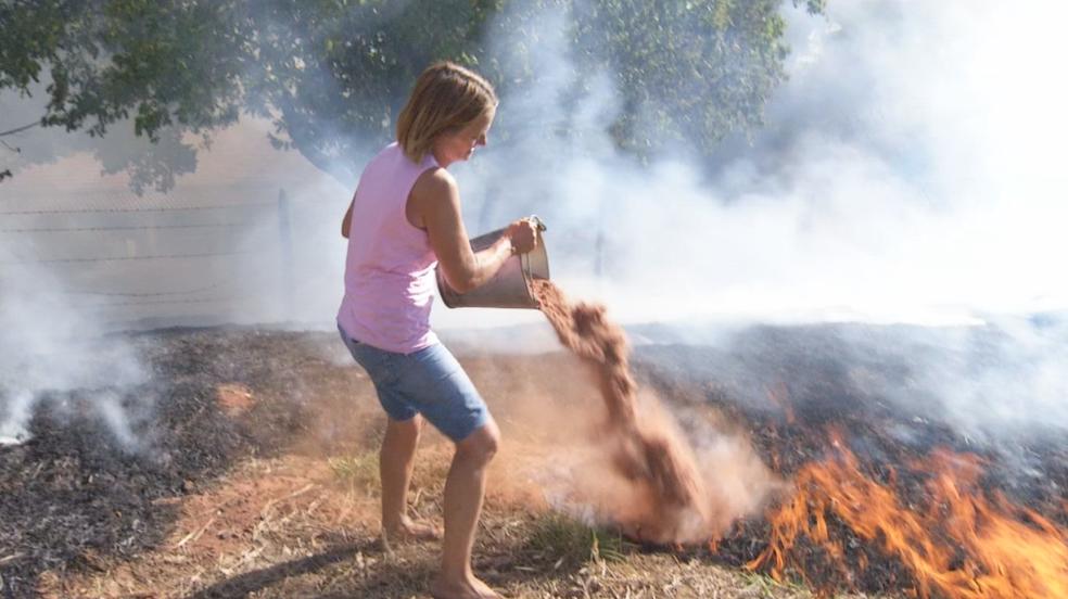 Moradora tenta controlar incêndio na região de Rio Preto (Foto: Reprodução/TV TEM)