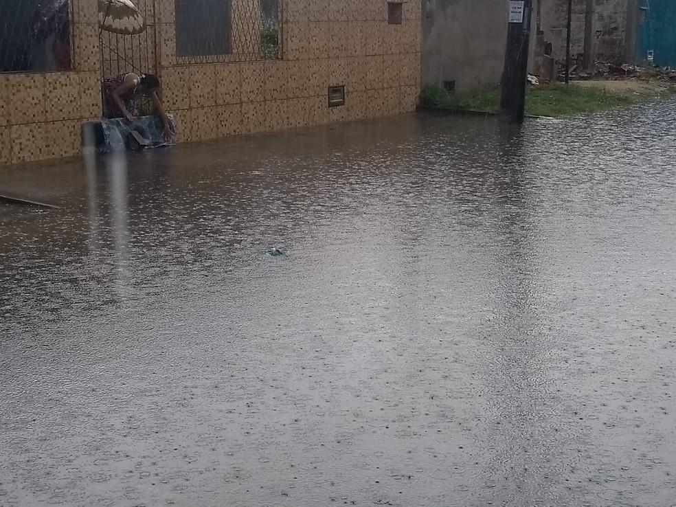 Moradora tenta impedir avanço da água na Rua Estivas, Zona Norte de Natal — Foto: Marcelo Henrique/Cedida