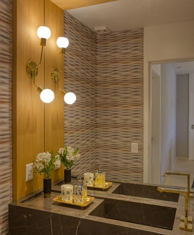 O lavabo segue uma linguagem contemporânea e sofisticada com o uso do mármore gris armani na bancada (Foto: MCA Estúdio/Divulgação/Produção: Núria Uliana)
