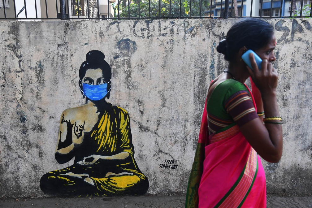 Mulher passa diante de um grafite de Buda usando uma máscara para evitar contágio em tempos de coronavírus, em Mumbai, na Índia, na segunda-feira (16) — Foto: Indranil Mukherjee/AFP