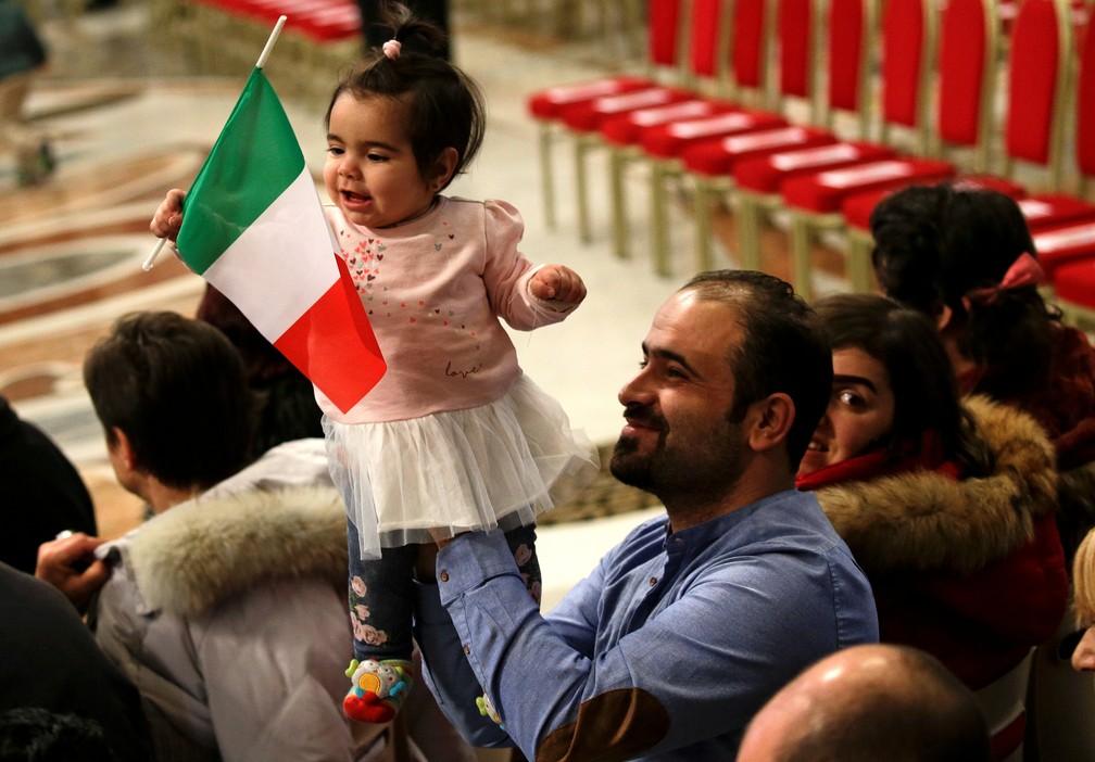 -  Imigrante segura sua filha com bandeira da Itália enquanto esperam pela missa em celebração ao dia Internacional dos Imigrantes, na Basílica de São P