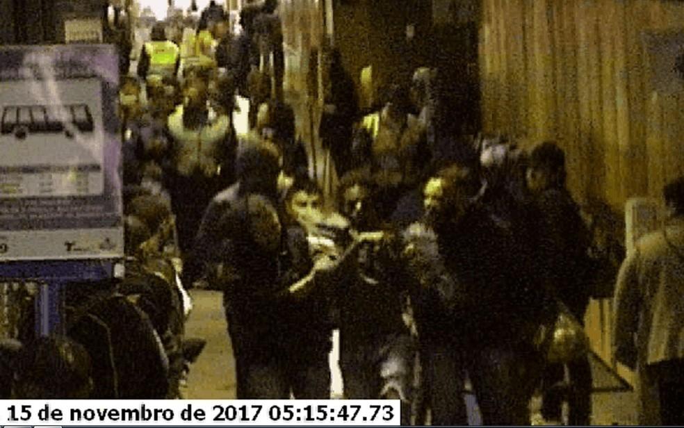 Diogo é levado por um grupo de rapazes para fora do terminal; ao fundo, os seguranças de jaleco (Foto: Reprodução/Câmeras de segurança)