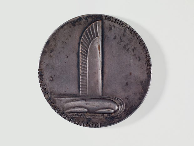 Medalha comemorativa do 25º aniversário da General Motors, 1933, Estados Unidos. Design: Norman Bel Geddes. Está incluída nos acervos do Metropolitan Museum of Art e do Cooper Hewitt Museum, ambos em Nova York, e do Wolfsonian Museum, em Miami