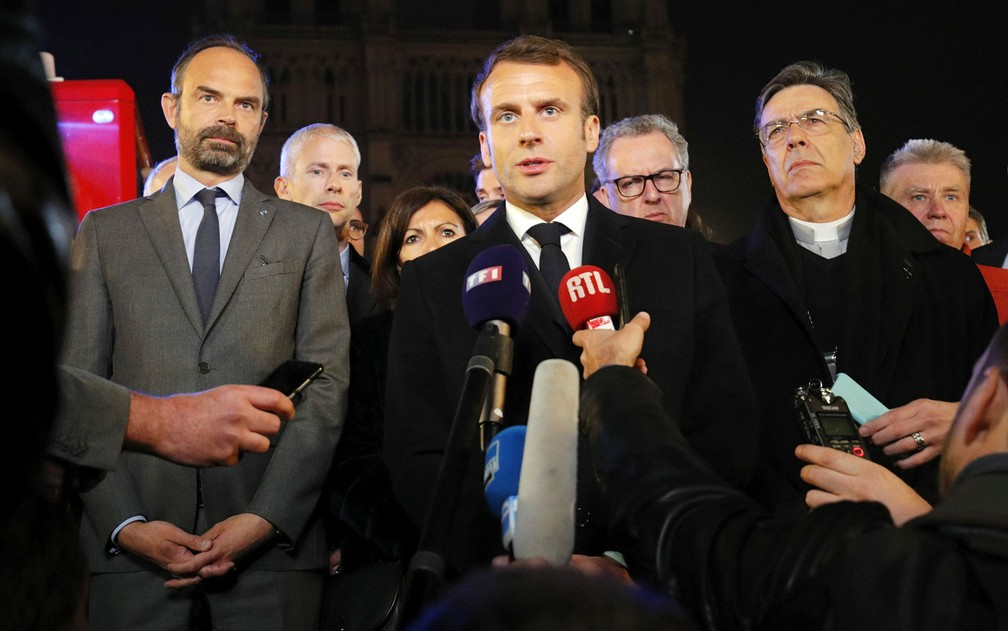 O presidente francês, Emmanuel Macron, ao lado do primeiro-ministro, Edouard Philippe, e do Arcebispo de Paris, Michel Aupetit, fala em frente à Catedral de Notre-Dame, em Paris, na segunda-feira (15) — Foto: Reuters/Philippe Wojazer/Pool