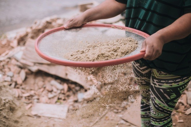 Mulher peneirando areia (Foto: Divulgação)