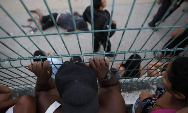 Pessoas olham para o corpo de um dos homens executados pela polícia do Rio, em 30 de março (Foto:  DIEGO HERCULANO AP )