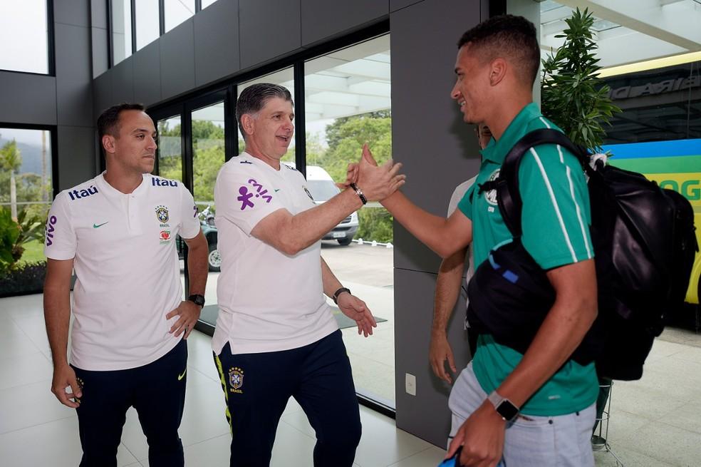 Técnico Guilherme Dalla Déa cumprimenta o zagueiro Henri, do Palmeiras, na chegada à Granja — Foto: Alexandre Loureiro/ CBF