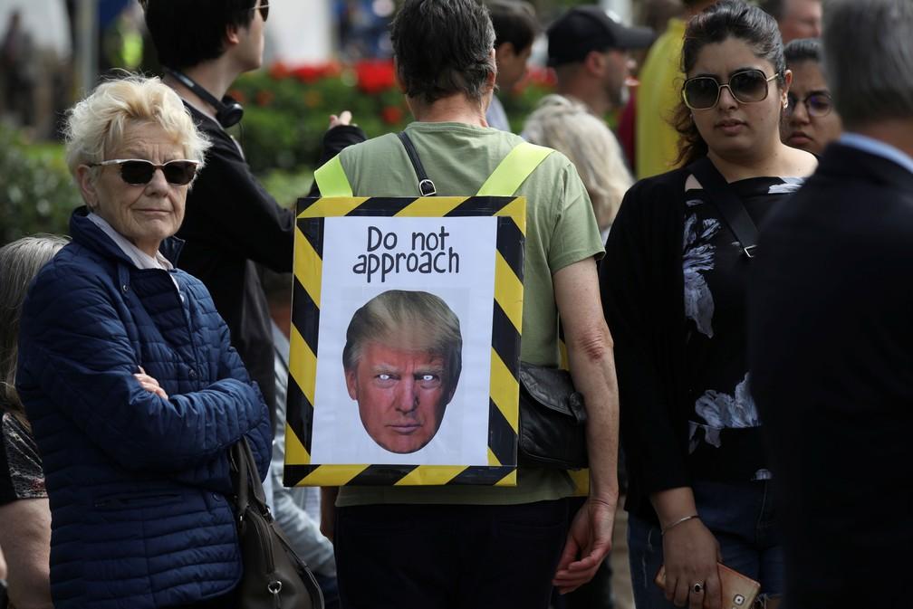 """Manifestante leva cartaz com uma foto do presidente dos EUA, Donald Trump, e a mensagem """"não se aproxime"""", perto do Palácio de Buckingham, nesta segunda-feira (3)  — Foto: Kevin Coombs/ Reuters"""