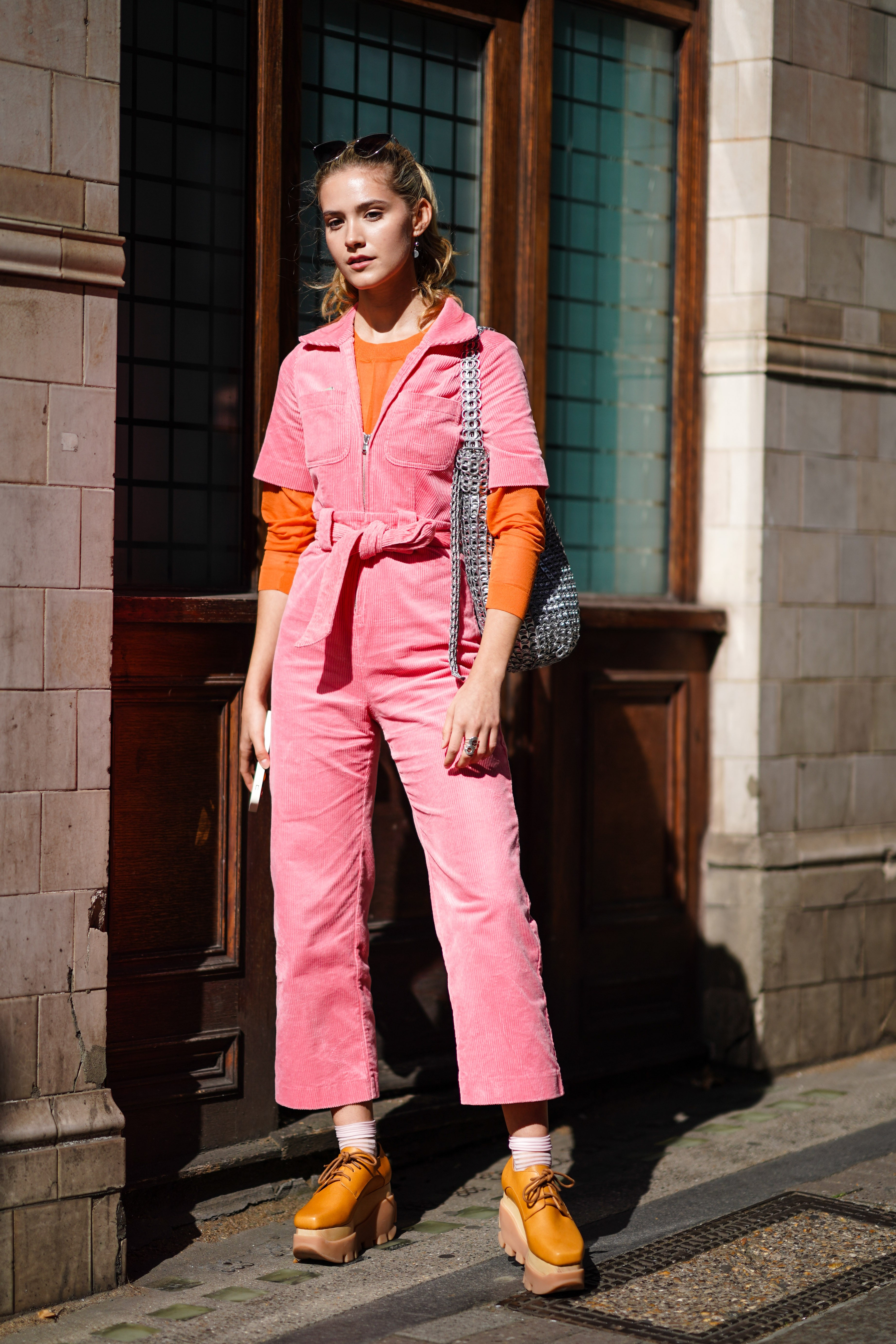 LONDON, ENGLAND - SEPTEMBER 13: Maddie Close wears a pink corduroy jumpsuit, a knitted belt, a silver metallic bag, an orange top, sunglasses over the head, a ring, brown platform shoes, during London Fashion Week September 2019 on September 13, 2019 in L (Foto: Getty Images)