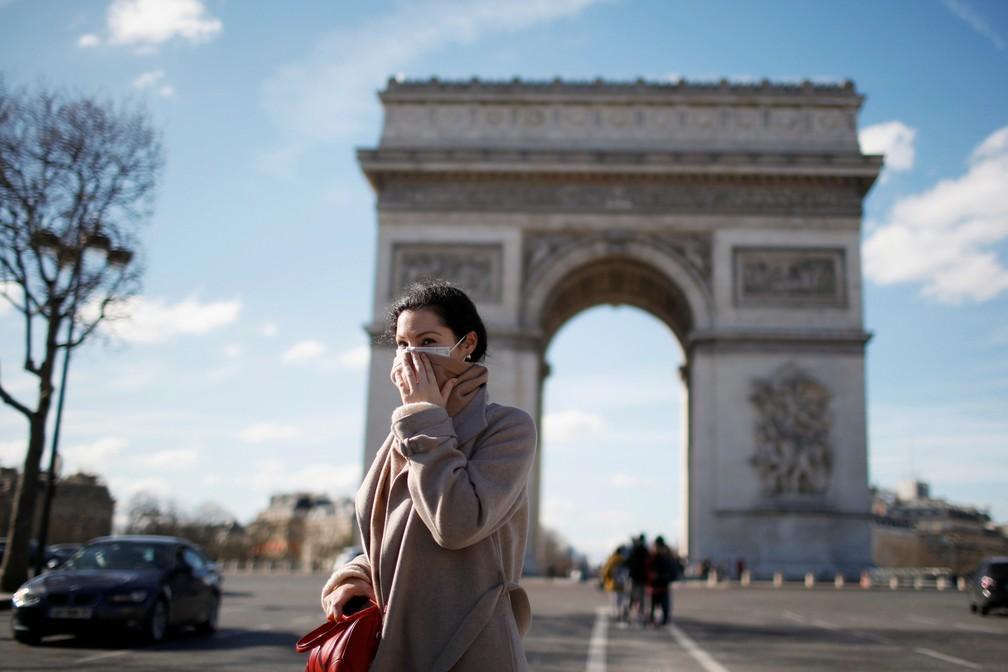 Uma mulher utilizando uma máscara de proteção caminha perto do Arco do Triunfo, em Paris, na França, neste domingo (15) — Foto: Gonzalo Fuentes/Reuters
