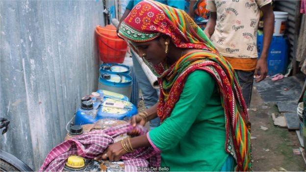 Fatima mostra como carrega contêineres pesados de água amarrando um pano para servir de alça (Foto: LOU DEL BELLO)