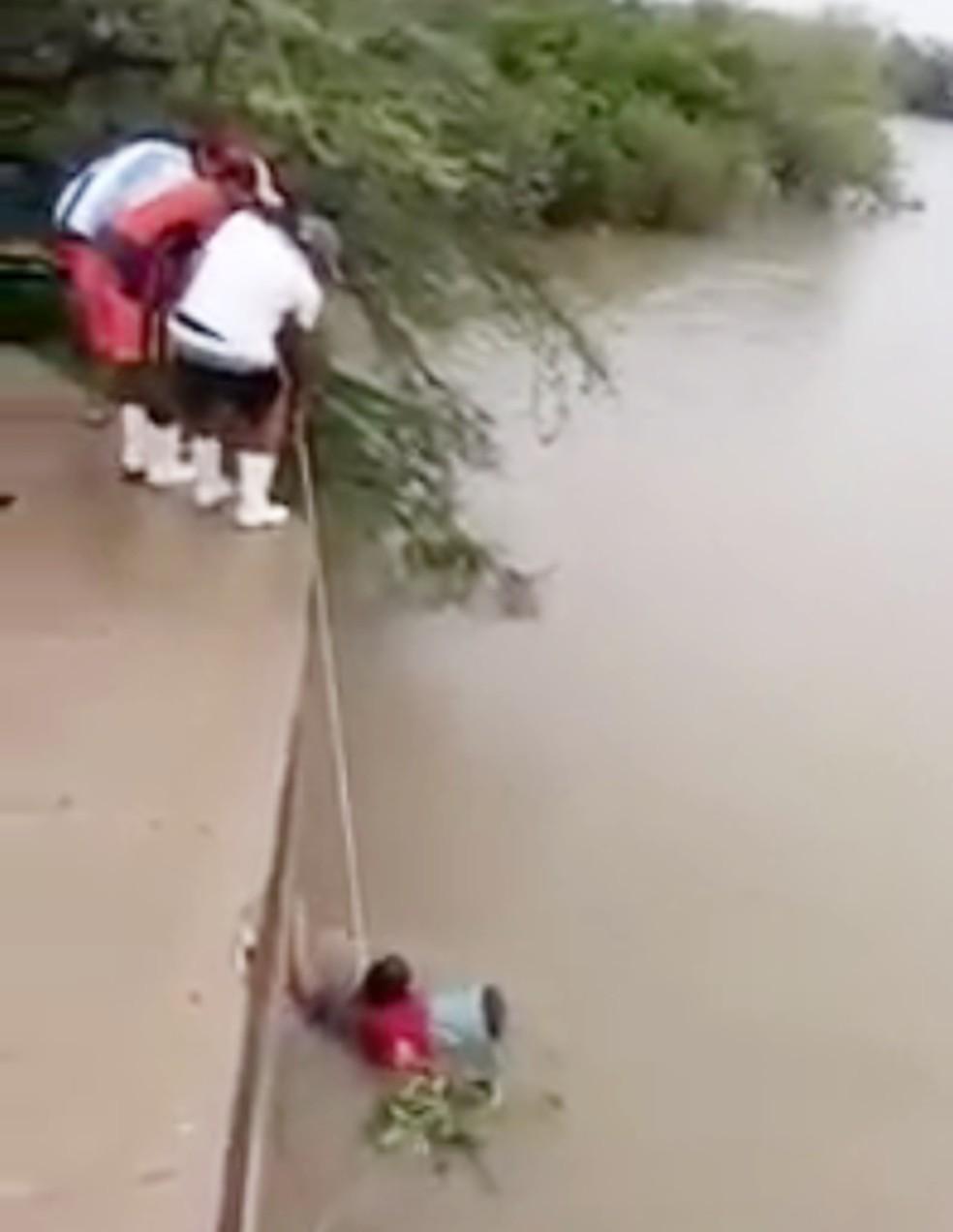 Pescadores foram retirados do rio por moradores da região, que usaram cordas para fazer o resgate (Foto: Reprodução/Vídeo)
