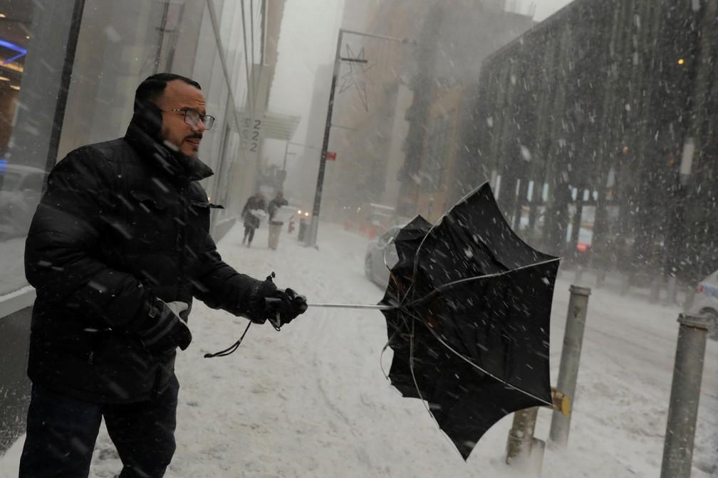 Homem segura guarda-chuva  que virou ao lado inverso durante neve em rua de Nova York (Foto: Lucas Jackson/Reuters)