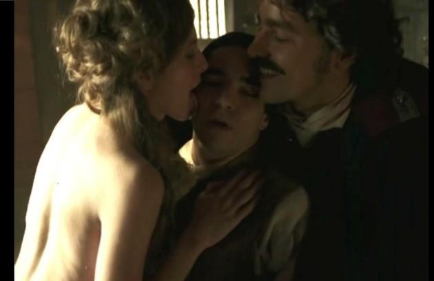 A relação de Tolentino (Ricardo Pereira) e André (Caio Blat) em 'Liberdade, liberdade' foi bastante comentada. Nesta cena, eles dão um beijo a três com a prostituta Gironda (Hanna Romanazzi) (Foto: Reprodução)