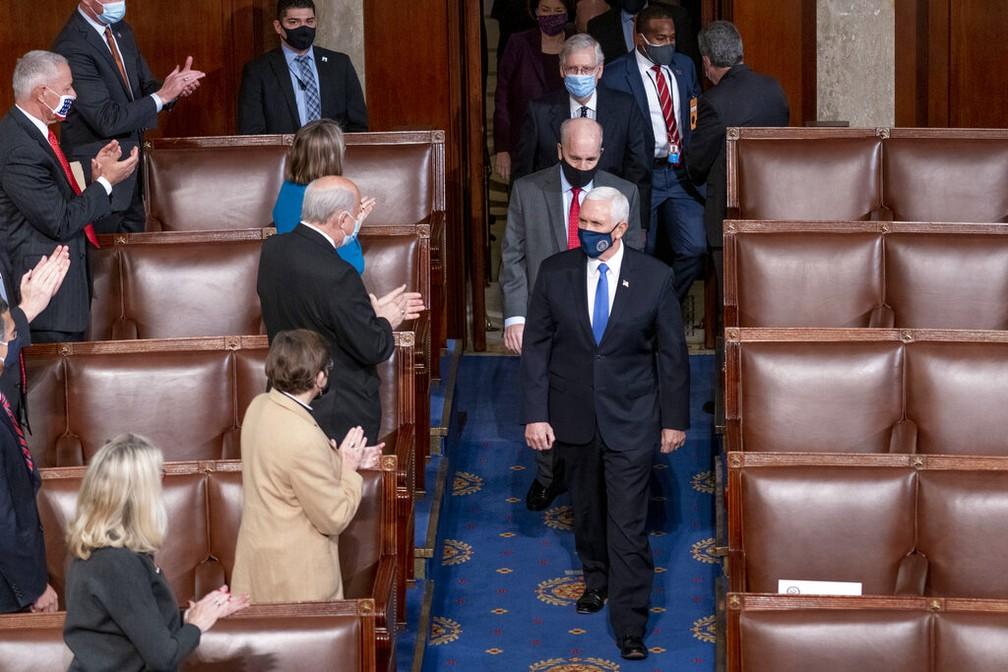 Mike Pence, vice-presidente dos EUA, e Mitch McConnell, líder republicano no Senado (acima, de máscara azul claro), chegam à sessão de contagem de votos no Congresso dos EUA nesta quarta-feira (6) — Foto: Andrew Harnik/AP Photo