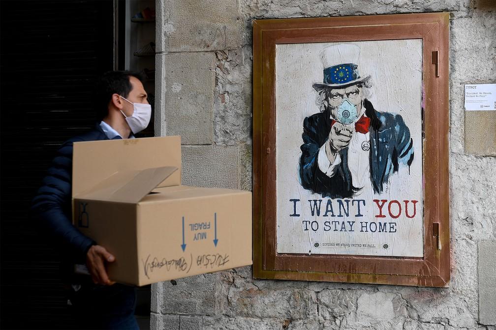 Pôster mostra o Tio Sam de máscara com a frase traduzida do inglês 'Eu quero que você fique em casa', alterando a fala usada para recrutar jovens para o Exército americano ('Eu quero você'), em rua de Barcelona, na Espanha. A obra do artista TVBoy é inspirada nos tempos de quarentena diante da pandemia do coronavírus — Foto: Josep Lago/AFP