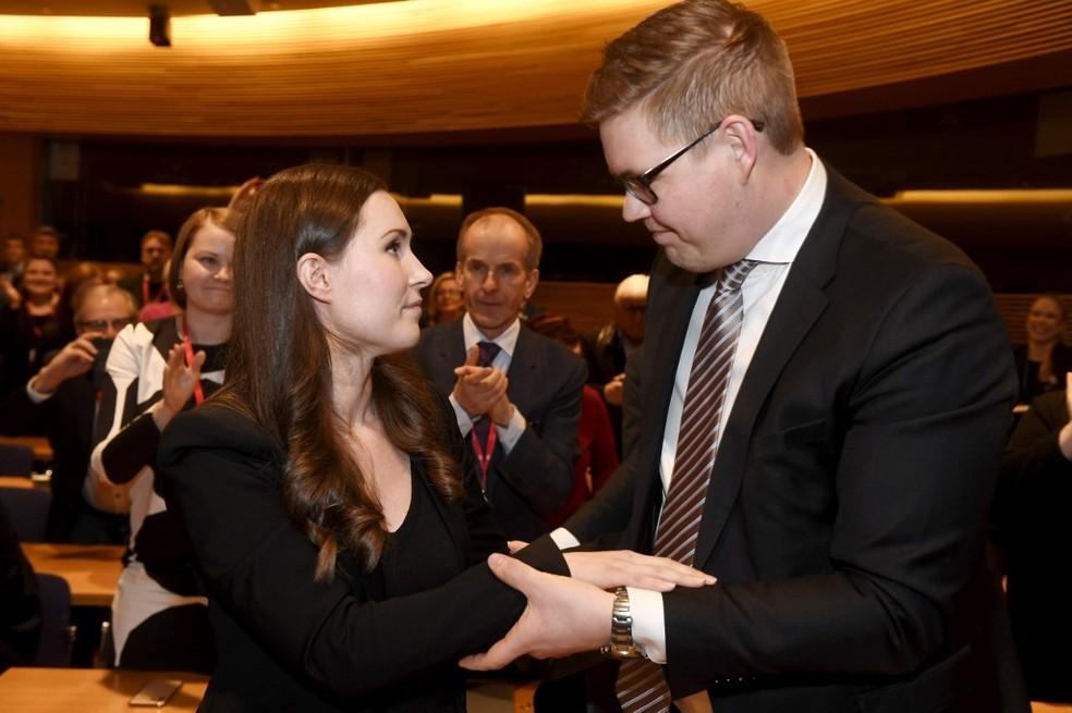 Sanna Marin recebe os cumprimentos do candidato que ela derrotou, Antti Lindtman, em 8 de dezembro de 2019 — Foto: Vesa Moilanen / Lehtikuva / AFP